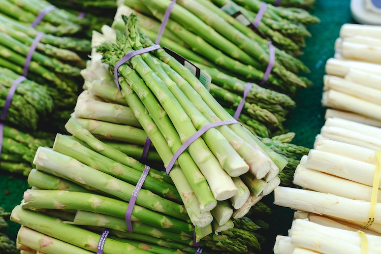 Bunches of fresh raw green organic asparagus vegetables for sale at farmers market. Vegan food concept. Stock photo green Asparagus Close up. Raw white and green asparagus at market.